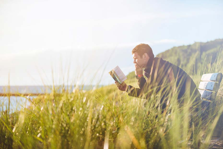 Man reading a book by the sea