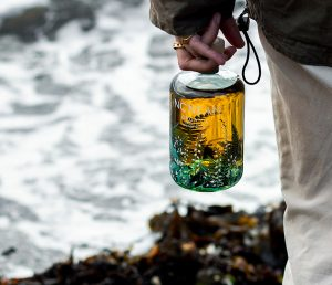 Person holding bottle of Nc'Nean Whisky by the sea