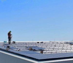 A man stands by solar panels on the roof at Fierce Whiskies