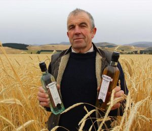 Belgrove Distillery founder holds two bottles of whisky in a field